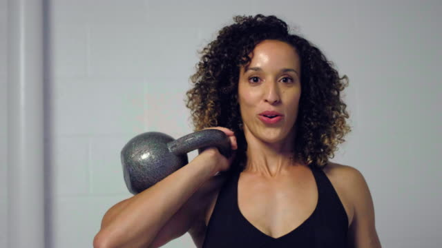 Young Woman Athlete Working Out with Kettleball