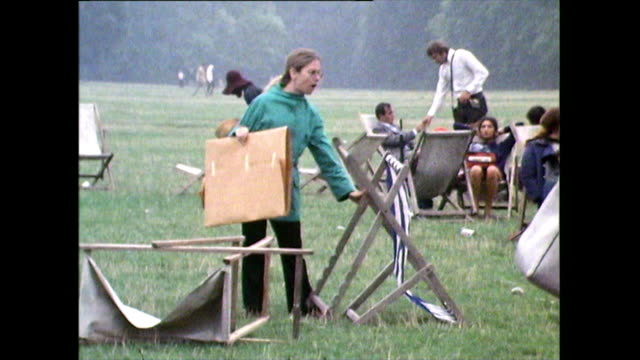 young woman attempts to set up deckchair in hyde park; 1971 - vignette stock videos & royalty-free footage