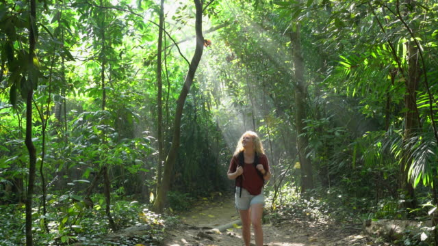 WS young woman backpacking through a forest