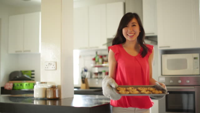 ms young woman baking cookies at home. - oven mitt stock videos and b-roll footage