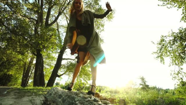 Young woman balances as she walks along a log