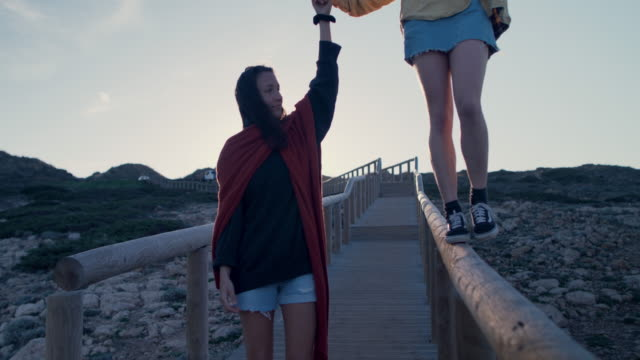 Young woman balancing on railing of beach walkway
