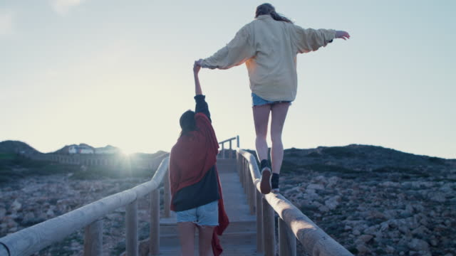 young woman balancing on railing of beach walkway - generation y stock-videos und b-roll-filmmaterial