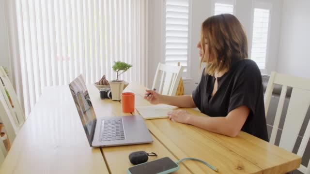 vidéos et rushes de jeune femme équilibrant le travail et la vie de famille - assis
