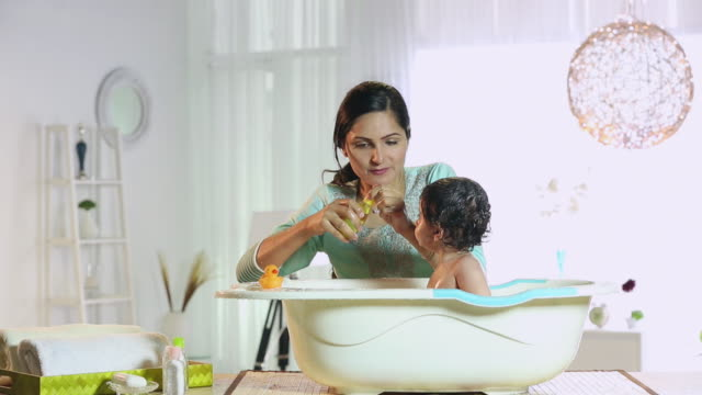 Young woman bathing her son