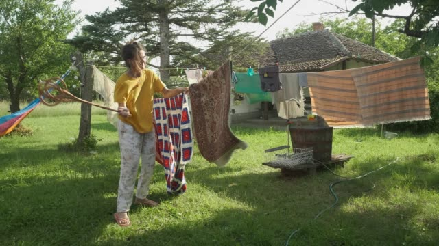 young woman beating a rug home cleaning - rug stock videos & royalty-free footage