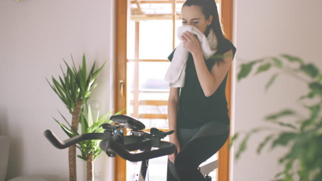 slo mo young woman being exhausted after intense training on the exercise bike - towel stock videos & royalty-free footage