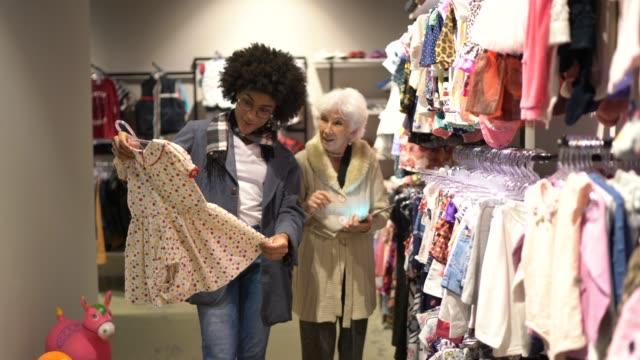 vidéos et rushes de jeune femme étant aidée par une vendeuse tout en faisant des emplettes pour des vêtements dans un magasin d'économie - vêtement de bébé