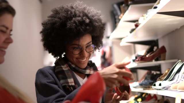 young woman being helped by a saleswoman while shopping for shoes in a thrift store - footwear stock videos & royalty-free footage