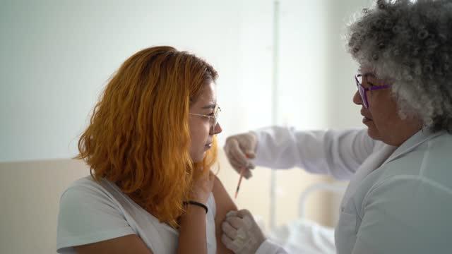 vídeos y material grabado en eventos de stock de mujer joven vacunada - epidemiología