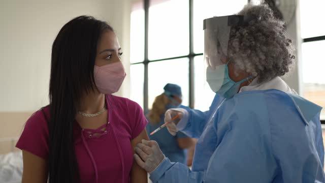 junge frau wird geimpft - mit gesichtsmaske - young women stock-videos und b-roll-filmmaterial