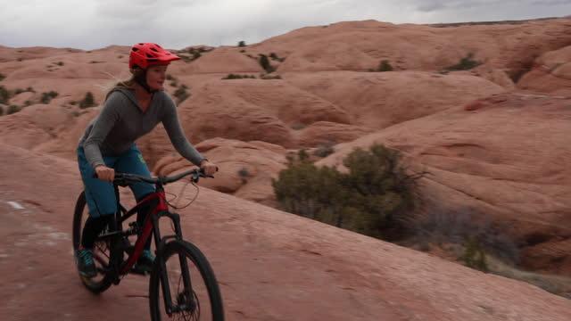 young woman bikes across slickrock rock slab, desert - moab utah stock videos & royalty-free footage