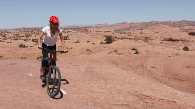 young woman bikes along slickrock rock slab - moab utah stock videos & royalty-free footage