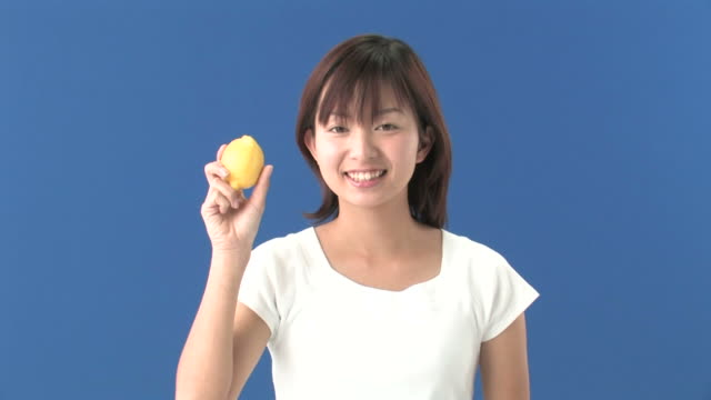 Young woman biting into lemon