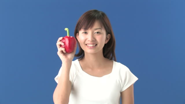 Young woman biting into red bell pepper