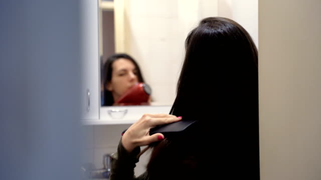 young woman blow drying hair - adjusting stock videos & royalty-free footage
