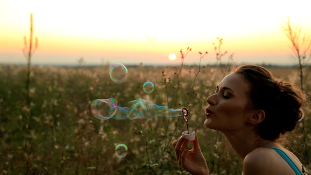 Young woman blowing bubbles in a field at sunset