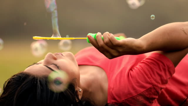 young woman blowing bubbles in the park, delhi, india - seifenblasenring stock-videos und b-roll-filmmaterial