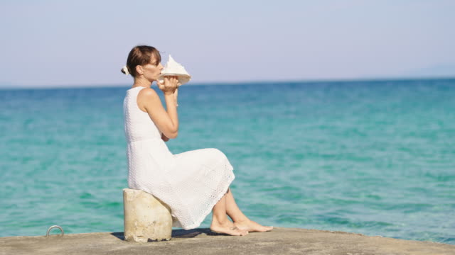 slo mo young woman blowing into a conch shell while sitting on a pier on the beach - conch stock videos & royalty-free footage