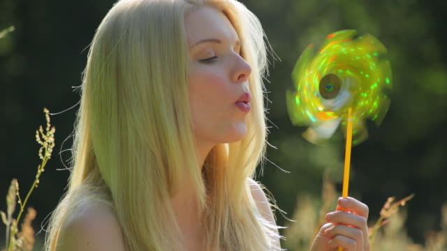 cu young woman blowing paper windmill in meadow / london, uk - windrad stock-videos und b-roll-filmmaterial