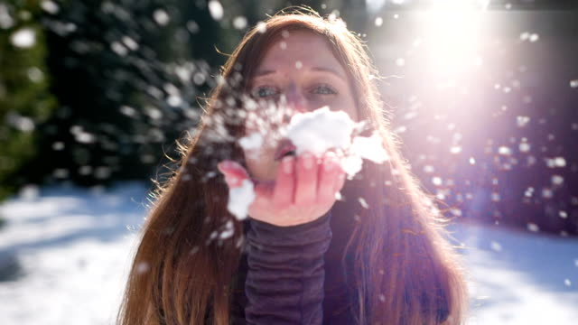 Young woman blowing snowflakes
