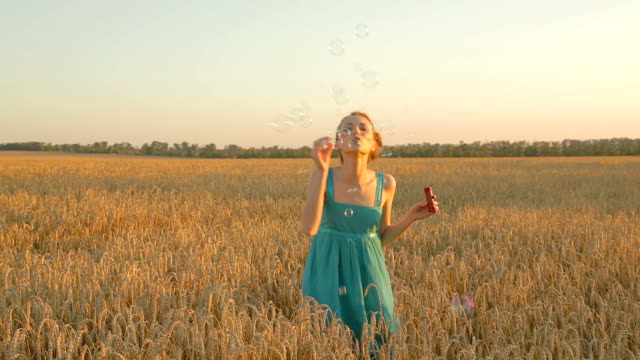 Young woman blowing soap bubbles outdoors in wheat field