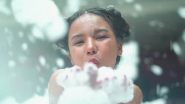 young woman blowing the soft soap sud bubbles at party - soap sud video stock e b–roll