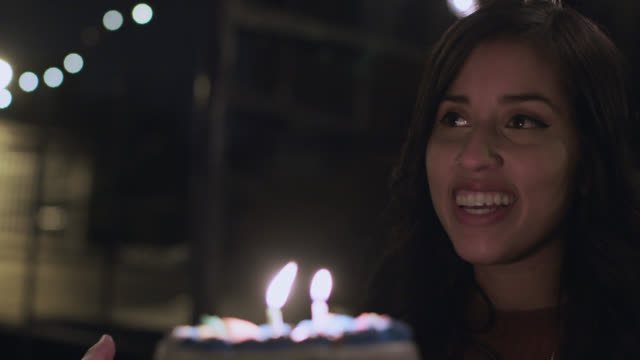 vídeos de stock e filmes b-roll de cu slo mo. young woman blows out candles on birthday cake and laughs with friends at rooftop party. - soprar