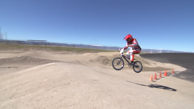 a young woman bmx rider riding bike on a dirt track.  - スタントバイク点の映像素材/bロール