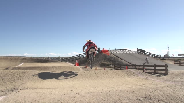 a young woman bmx rider riding on dirt track. - スタントバイク点の映像素材/bロール