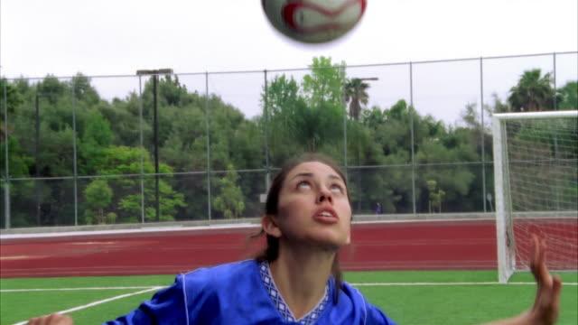 SLO MO, CU, Young woman bouncing soccer ball on head, Biola University, La Mirada, California, USA