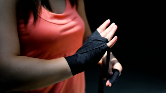young woman boxer getting her fists ready for the boxing gloves by wrapping bandage - avvolto video stock e b–roll