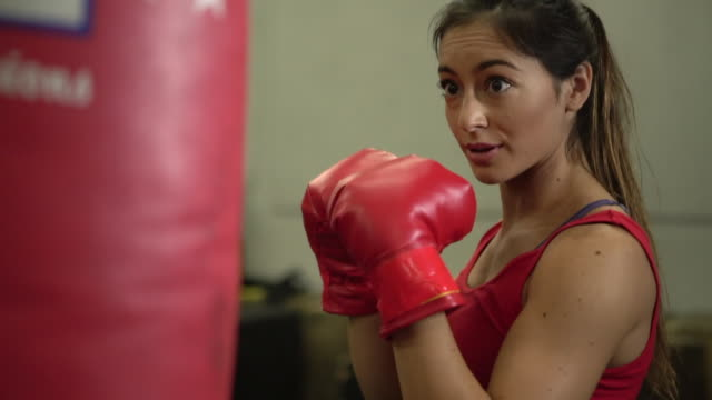 stockvideo's en b-roll-footage met cu young woman boxing in a gym - stootzak fitnessapparatuur