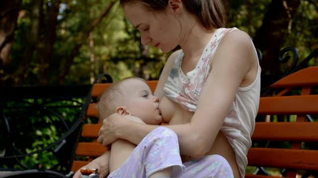 vídeos y material grabado en eventos de stock de joven mujer amamantando su bebé - breastfeeding