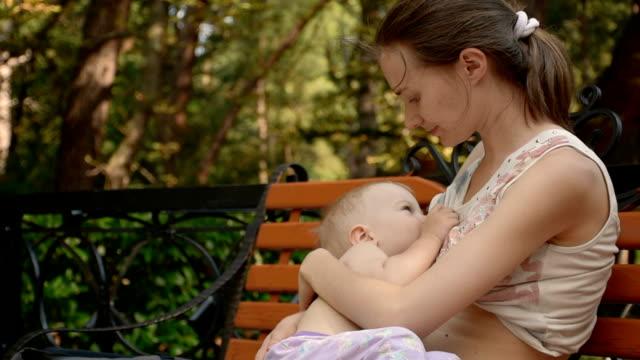 vídeos y material grabado en eventos de stock de joven mujer amamantando su bebé - amamantar