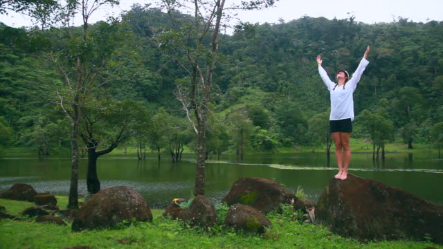Young woman breathing fresh air in rainforest