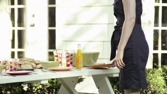 Young woman bringing plate to picnic table, sitting down and smiling