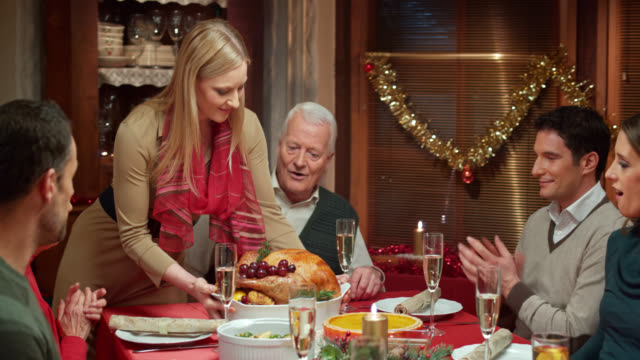 Young woman bringing turkey to family at the table