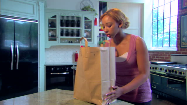 vidéos et rushes de young woman brings a bag of groceries home and puts it on the counter. - sac de shopping