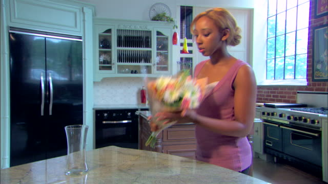 a young woman brings a bouquet of flowers into her kitchen. - vase stock videos & royalty-free footage