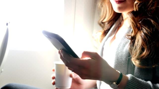 Jonge vrouw surft op smartphone, terwijl op het vliegtuig