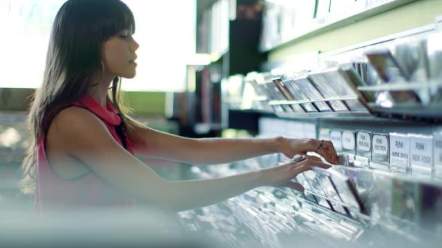 vídeos de stock e filmes b-roll de ms a young woman browses through a rack of vintage records - escolha