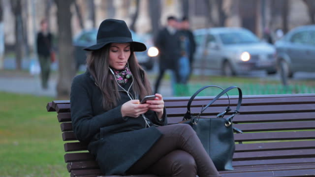 young woman browsing her smart phone and listening to music in the city at the end of the day. - bench stock videos & royalty-free footage