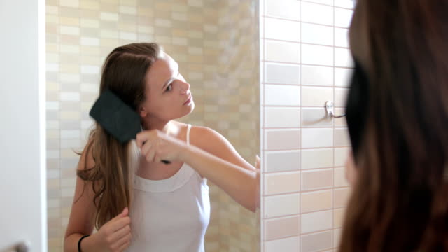 young woman brushing healthy hair in front of a mirror.yawning, stretching - coda di cavallo video stock e b–roll