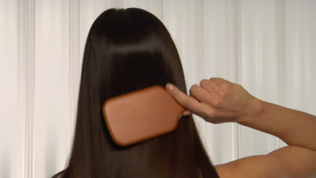 CU, Young woman brushing her long brown hair, rear view