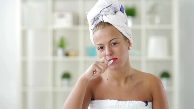young woman brushing her teeth - wrapped in a towel stock videos & royalty-free footage
