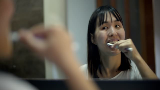 young woman brushing teeth in bathroom - toothpaste stock videos and b-roll footage