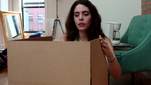 vídeos y material grabado en eventos de stock de young woman builds a cardboard box - reubicación