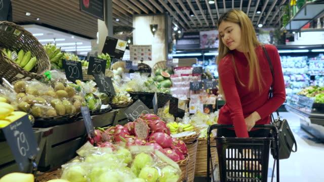 若い女性は果物やスーパーで野菜を購入します。 - 生鮮食品コーナー点の映像素材/bロール