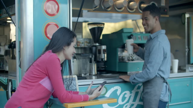 young woman buying coffee at a coffee truck - selling stock videos & royalty-free footage